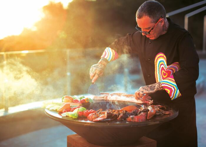 Man cooks on the OFYR Fire bowl