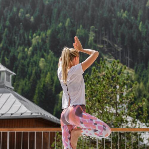 Woman doing yoga on the fitness terrace with mountain view