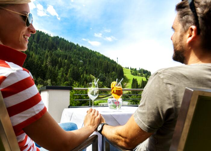 Guests enjoy cocktail with view on mountains on Wagrain