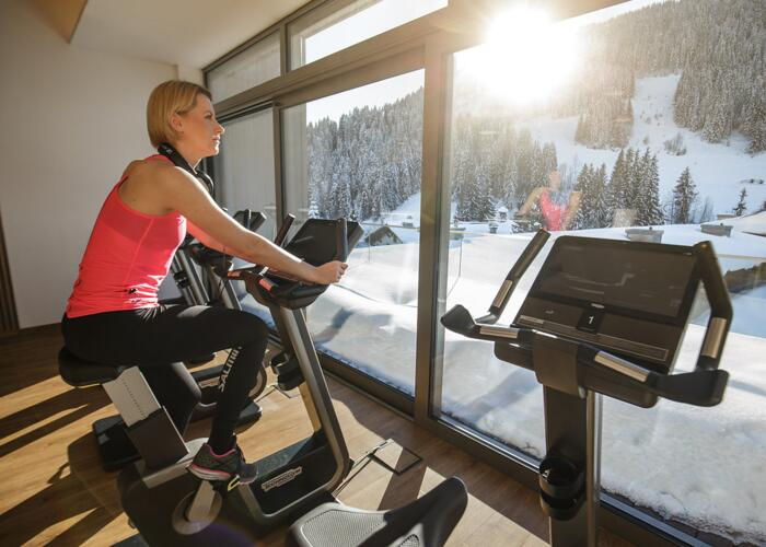 Woman in fitness center on bycicle with view on Grafenberg